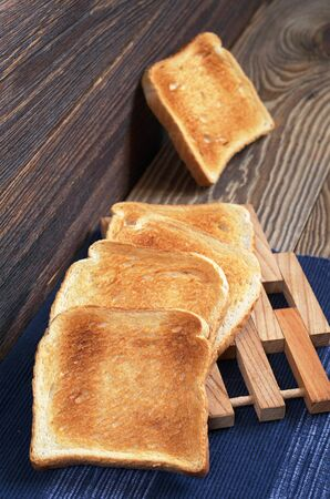Slices of toasted bread on old wooden table. Vertical composition