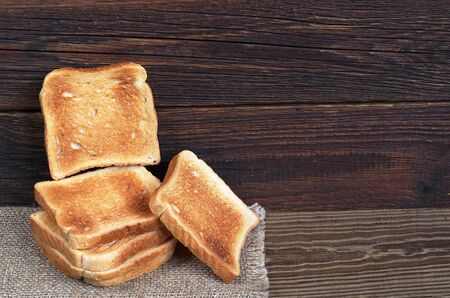 Slices of toasted bread on the dark wooden table, Space for text Stock Photo