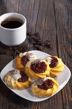 Cookies with jam and sugar icing and cup of hot coffee on dark wooden table