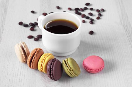 French macaroons and cup of coffee on light wooden background