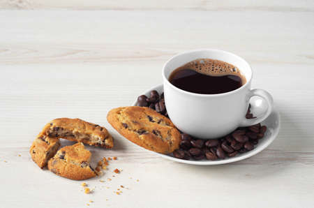 Cup of coffee and chocolate chip cookies on light wooden table