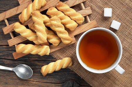 Cup of tea and homemade shortbread cookies on rustic wooden table, top view 免版税图像