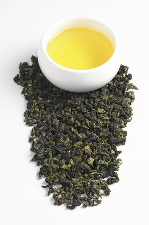 Dry green tea leaves scattered and beverage in cup on a white background. Tie Guan Yin
