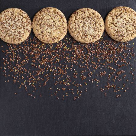 Cookies with flaxseeds and sesame on black stone background, top view with space for text