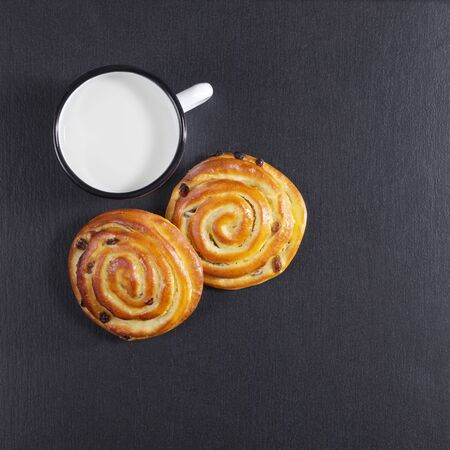 Buns with raisins and enameled mug of milk on a background of black stone, top view