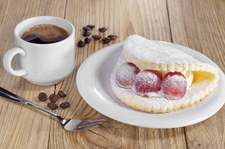 Cake with grape berries, sprinkled with powdered sugar in plate and cup of coffee on the wooden table Archivio Fotografico - 99848192