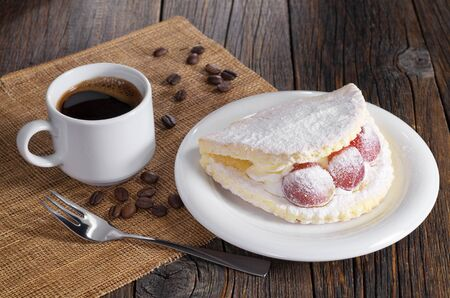 Cup of coffee and cake with grape berries, sprinkled with powdered sugar in plate on old wooden table Archivio Fotografico - 99940386