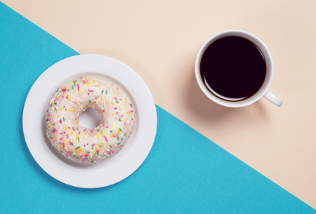 Cup of coffee and tasty donut with glaze and colorful sprinkles is located on an light brown and blue background, top view Stock Photo - 101537359