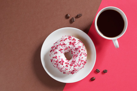 Donut with cream cheese sprinkled of red crumbs in a white plate and a cup of black coffee on a colorful background, top view