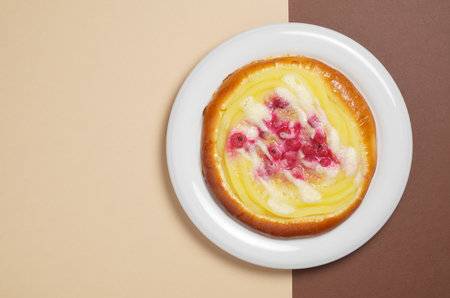 Bun with custard and red currant in plate on a colored background, top view with copy space