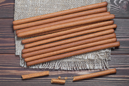 Heap of rye bread sticks on burlap is located on brown wooden background, top view
