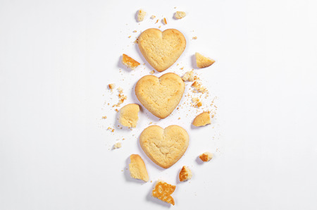 Shortbread cookies in shape of heart whole end broken on white background, top view with space for text