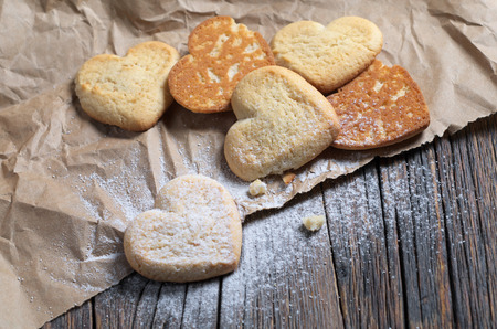 Heart-shaped shortbreads sprinkled with powdered sugar on brown crumpled paper located on old wood Banco de Imagens