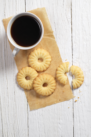 Top view of shortbread cookies and cup of coffee on white wooden table