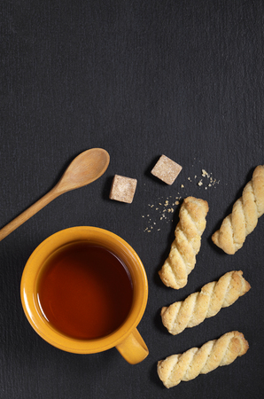 Cup of tea and shortbread cookies on black stone background, top view. At the top there is a place for text