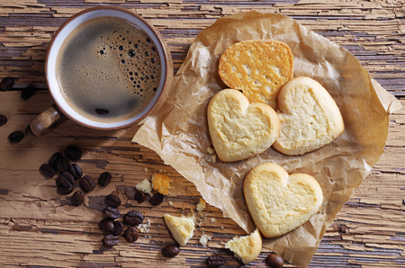 Cup of coffee and cookies in shape of heart on paper located on the old wooden table, top view