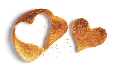 Roasted white bread with a cut out heart-shaped piece on a white background, top view Banco de Imagens