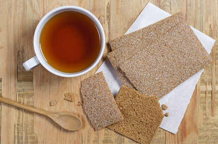Cup of tea and low-calorie crispy bread on an old wooden background, top view
