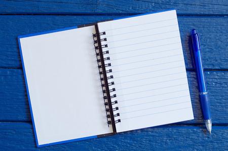 Öffnen Sie Notizblock mit einem Stift auf blauem Holztisch, Ansicht von oben. Platz für Ihren Text