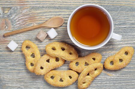 Cup of tea and tasty pretzels with sugar on old wooden background, top view