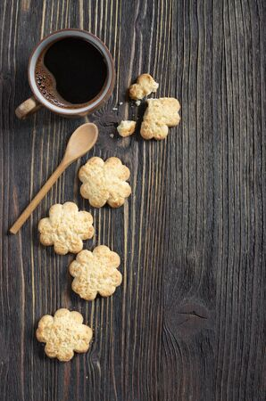 Biscuits with coconut chips and cup of coffee on the background of an old wooden table, top view with space for text