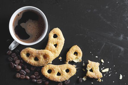 Cup of coffee and pretzels with sugar on old black metal background, top view