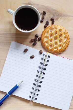 Notebook, coffee and cakes with apple filling on old wooden background, top view with copy space Reklamní fotografie