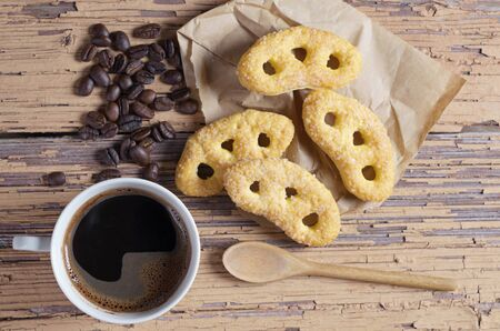 Cup of coffee and pretzels with sugar on old wooden background, top view