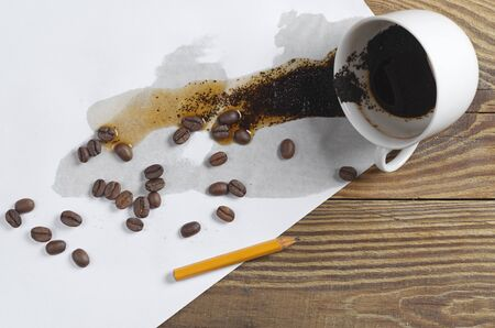 Conceptual photo with spilled coffee and a broken pencil on wooden desk, top view