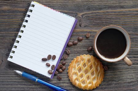 Notebook, coffee and cakes with apple filling on old wooden background, top view