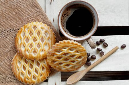 Cup of coffee and lattice cakes with apple filling and brown sugar in wooden spoon, top view Reklamní fotografie