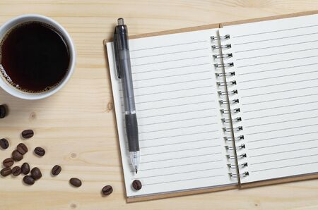 Open notepad with a pen and cup of coffee on wooden desk, top view