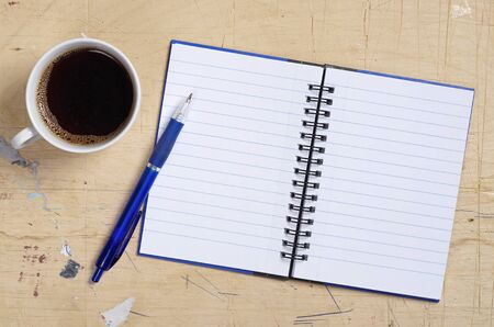 Spiral Note Pad with Pen and cup of coffee on old wooden background, top view