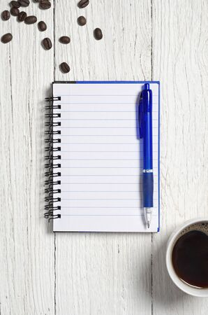 Notebook, pen and cup of coffee on old white wooden table, top view