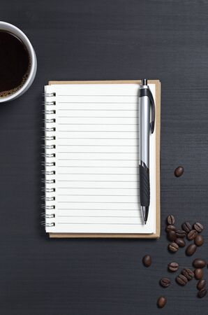 Notepad with pen and cup of coffee on black wooden table, top view Reklamní fotografie
