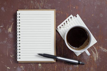 Notepad with a pen and cup of coffee on a dirty table, top view