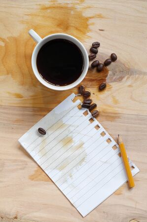 Conceptual photo with spilled coffee and sheet of notebook on wooden table, top view  Reklamní fotografie
