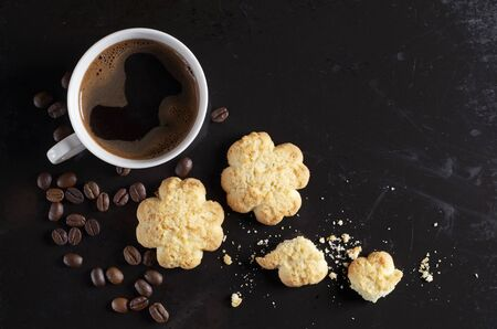 Cup of coffee and biscuits with coconut chips on old black background, top view  Reklamní fotografie