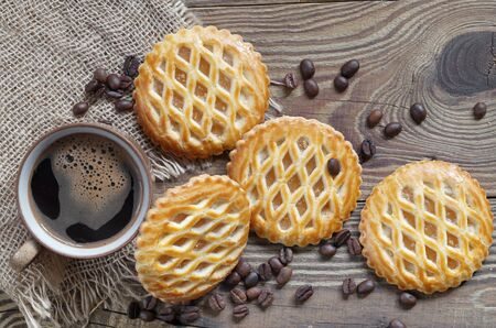 Cup of coffee and cookies with an apple filling, located on wooden background, top view  Reklamní fotografie