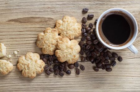 Cup of coffee and shortbread with coconut chips on old wooden background, top view  Reklamní fotografie