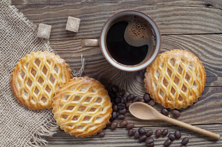 Cup of Coffee and Round Apple Lattice Cakes on wooden background, top view