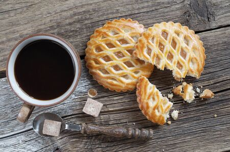 Lattice topped pastries with apple filling and cup of coffee on old wooden background, top view