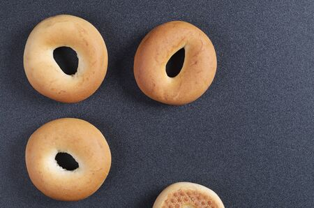Top view of classic bagels on black background