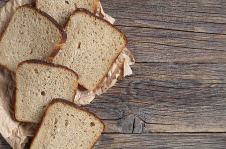 Slices of rye bread on paper, on an old wooden table, top view with copy space Reklamní fotografie