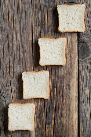 From above pieces of mini toasts against old wooden background