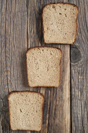 From above pieces of fresh rye bread against old wooden background Reklamní fotografie