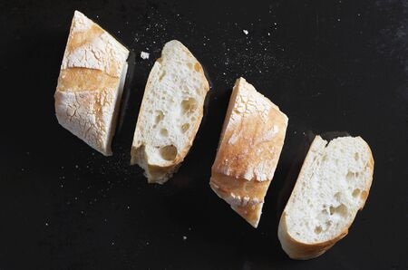 From above pieces of fresh bread arranged in line against black metal background Reklamní fotografie