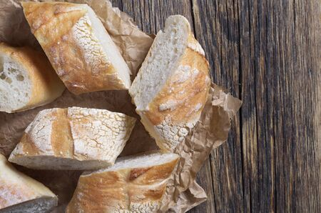 Crunchy slices of fresh bread arranged in pile on parchment paper on rustic table Reklamní fotografie