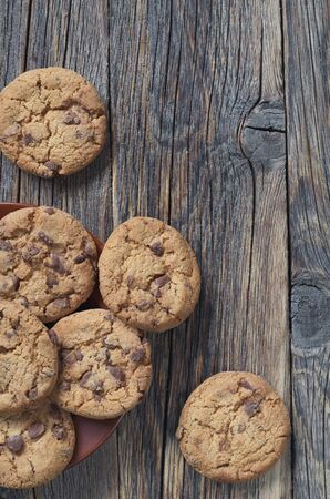 Chocolate chip cookies on old wooden table, top view with copy space