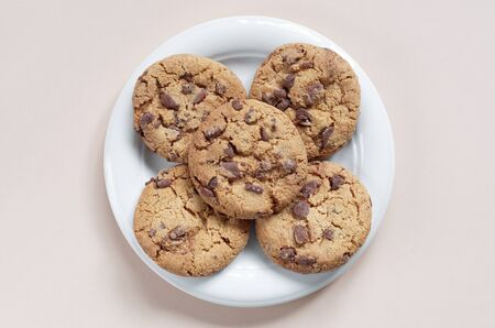 Chocolate chip cookies in plate on a light background, top view